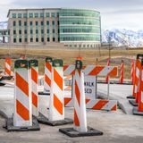 Clear Square Sidewalk Closed sign and road safety poles on a paved road under repair. In the background is a modern building with skybridge and snowy mountain royalty free stock photo