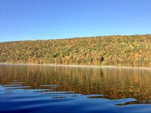 Canadice Lake, one of New York`s Finger Lakes. The clear, still water of Canadice Lake, one of Finger Lakes in New York, in horizontal orientation in Autumn stock image