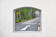 Clear story idea: words of startup with white arrow on road, business concept. Words of startup with white arrow on road surface on clear story window on white Stock Photography