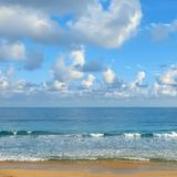 Clear sunny day at seaside. Yellow sand and blue ocean Stock Photo