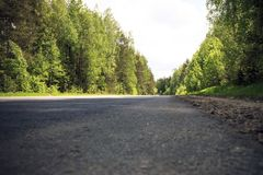 A clear, sunny day. Summer. Forest - all green and blue sky. And the road is asphalt. Stock Photography