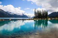 Emerald waters of Garibaldi Lake reflect bottle-green tree sihouettes stock photography