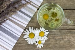 Clear transparent cup of camomile tea on vintage wooden background with dried herbs and daisy flowers. royalty free stock images