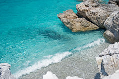 Clear Turquoise Sea Water, Stones and Wave. Greece. Royalty Free Stock Photo