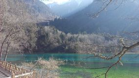 Clear view of blue crisp water of beautiful lake with mountain scene stock photography