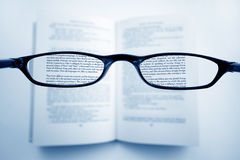 Clear Vision. A pair of glasses above a book, in the lenses, all is clear, outside, is blurred. ** Note to the inspector, The text is a non copyrighted classic stock photography