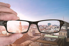 Clear vision. Through glasses, hand holding eyeglasses with cityscape in background Stock Image