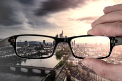 Clear vision. Through glasses, hand holding eyeglasses with cityscape in background Stock Images