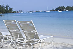 Clear water beach. Crystal clear blue water beach with beach chairs Stock Images