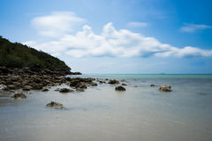 Clear water beach. With black rock stock images