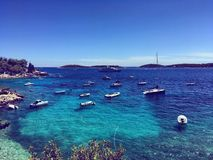 Blue Croatian beach. Clear water and boats on sunny beach in Croatia Stock Photos
