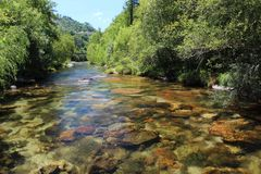 Clear water at Cavado River - 2. Water stream with a small waterfall. Clean, transparent, pristine water near a hydroelectric power station in Cavado River stock image
