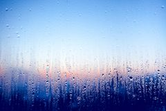 Clear water drops on the glass window. Background. Clear water drops on the surface of the glass window. Color transition .Light blue, white, pink, dark blue Stock Photography