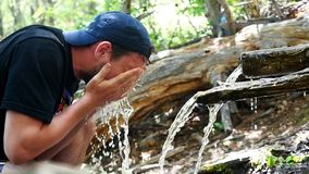 Clear water flowing into a man`s hands. Young man washes her face on nature. slow motion. 1920x1080. Clear water flowing into a woman`s hand. Young woman drinks stock footage