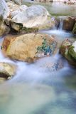 Clear water flowing over rocks Stock Image