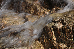 Clear water flows over pink granite rocks. Clear mountain water flows in a mini waterfall over pink tinged hard granite rock. Granite is a very hard igneous rock Stock Image