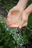 Clear water. She is gaining hands pure water from a spring Royalty Free Stock Images
