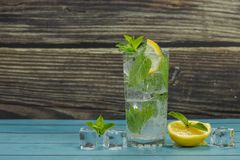 Clear water in glass with green mint leaves and ice cubes royalty free stock photography