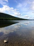 Clear water lake mirroring mountain and clouds Royalty Free Stock Photo