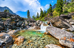 Clear water of a mountain stream and a small waterfall. In a natural basin between large boulders . Eastern Sayan Royalty Free Stock Photos