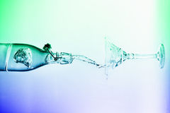 Clear water pour horizontal out of bottle splash into glass with Stock Image