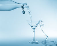 Clear water pour out of bottle splash into glass and spill with Royalty Free Stock Photos