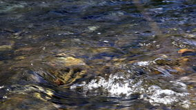 Clear water runs along the river creating a funnel of wind and pitfalls stock footage