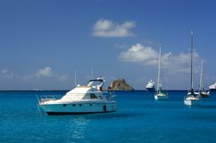 Clear water, tropical island, yachts and boats Stock Images