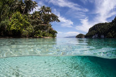 Clear Water and Tropical Islands. Warm, clear water bathes a tropical island in Raja Ampat, Indonesia. This beautiful region is known to harbor high marine Stock Image