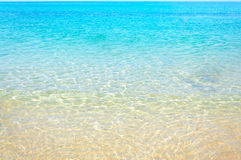 Clear water and wave of the sea on the sand beach with sunlight Royalty Free Stock Images
