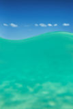 Clear waterline caribbean sea underwater and over with blue sky Stock Images