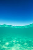 Clear waterline caribbean sea underwater and over with blue sky. Tropical horizon Royalty Free Stock Images