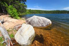 Clear Waters of Northwoods Wisconsin. Huge boulder along the shoreline of Buffalo Lake in the Northern Highland-American Legion State Forest of Wisconsin royalty free stock photos