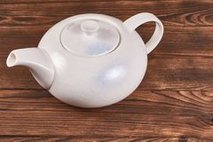 Clear white ceramic kettle. With delicate ornament on wooden background stock photo