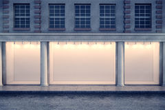 Clear window shop at night. Front view of building with illuminated clear window shop and columns in night city. Advertisement and commerce concept. Mock up, 3D royalty free illustration