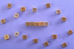 Clear word metal block. Clear word gold and silver metal block on blue paper with letter blocks around Stock Photography