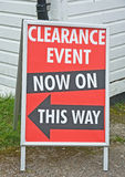 Clearance event. Sign on board with text reading ' Clearance Event now on  this way ,'  with black arrow pointing Stock Photography