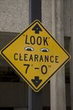 Clearance Sign. A yellow 7 foot clearance sign with little eyes drawn on it saying look to call a person's attention royalty free stock photos