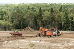 Clearcut forest deforest machines trucks excavator in New Brunswick Canada. Clearcut forest deforest with machines trucks excavator in New Brunswick Canada Royalty Free Stock Image