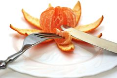 Cleared mandarine on a plate, plug, knife. Royalty Free Stock Photos