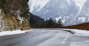 Cleared road in the Alps and the snow and rocks Stock Photo