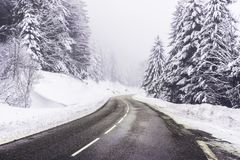 Cleared road curve in winter. A cleared road curve in a snowy pine forest during a foggy day of winter, Vosges mountains, France Stock Photo