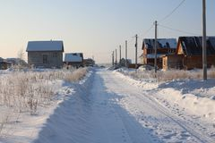 Cleared wide road winter drive  private houses in the Siberian village among the snowdrifts through the forest on a clear winter. Cleared wide road winter drive royalty free stock images