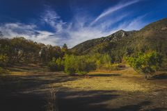 Oak Glen Preserve Trail. Clearing in the forest with tree-covered mountains in the background and clouds in the sky along a hiking trail in autumn, Oak Glen Royalty Free Stock Images