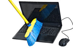Clearing laptop of viruses. Concept. Antivirus. broom sweeps the laptop keyboard Stock Photos