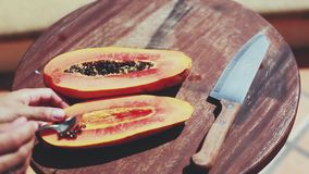 Clearing a papaya fruit preparing for eating or making smoothies. 1920x1080. Hd stock video footage
