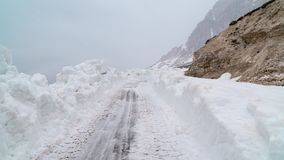 Clearing the road from snow in the mountains. Bad weather in the mountains. Blizzard. royalty free stock image