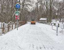 Clearing a sidewalk from snow. A snowplough clearing a sidewalk from snow Stock Photo