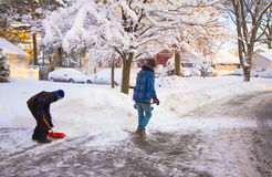 Clearing Snow. A father and two sons at dawn clearing snow after a heavy snowstorm Stock Image