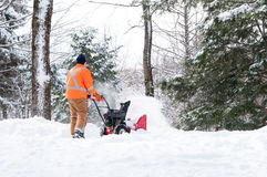 Clearing snow. Man using a snow blower to clear a driveway royalty free stock image